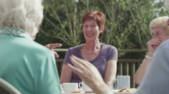 Happy group of senior friends chatting and laughing with cups of tea outdoors - stock footage
