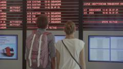 Man and woman looking at the schedule of trains at the station - stock footage