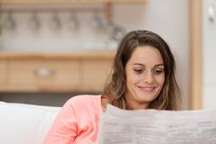 Young woman catching up on the morning news Stock Photos