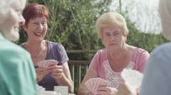 Happy group of senior female friends playing cards in the garden - stock footage