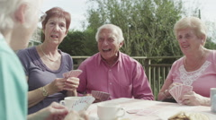 Happy group of senior friends playing cards in the garden with cups of tea - stock footage