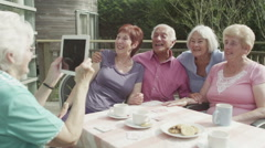 Happy group of senior friends pose to take a picture with computer tablet - stock footage