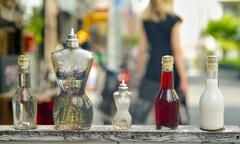 Perfume bottles shaped like the female body with a out of focus woman Stock Photos