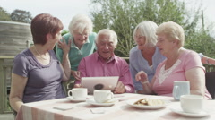 Happy group of senior friends laughing at what they see on computer tablet - stock footage