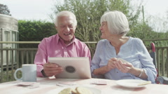 Happy senior couple laughing at something they see on a computer tablet - stock footage
