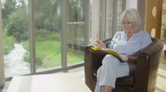 Senior lady sits by the window reading a book in retirement home Stock Footage