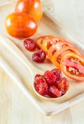 fresh and dried tomatoes wood plate - stock photo