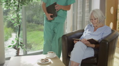 Caring nurse or doctor discussing medical notes with elderly female patient - stock footage