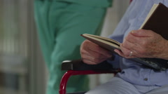 Close up caring nurse holding hand of elderly female patient in a wheelchair Stock Footage