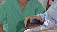 Caring male nurse giving support to elderly female patient in care home - stock footage