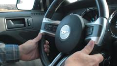 Closeup of an Elderly Man's Hands Driving a Ford Mustang Stock Footage