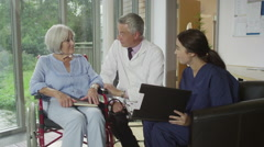 Caring doctor and nurse discussing medical notes with elderly female patient Stock Footage
