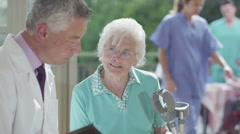 Caring doctor discussing medical notes with elderly female patient - stock footage