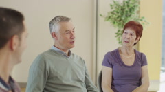 Mature people in group therapy session talk about their problems together - stock footage