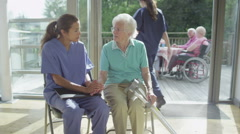 Caring nurse giving support to elderly female patient in care home - stock footage