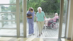 Caring nurse helping elderly female patient to walk in hospital or care home Stock Footage