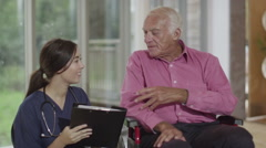 Caring nurse giving support to elderly male patient in a wheelchair - stock footage
