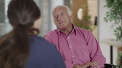 Caring nurse giving support to elderly male patient in a wheelchair Stock Footage