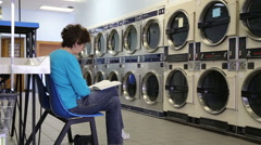 Woman reading in a laundrymat Stock Footage