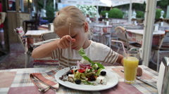 Little girl eating a Greek salad in the cafe and looking at the camera Stock Footage