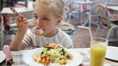 Girl eating big shrimp in a restaurant. She loves fish restaurant Stock Footage