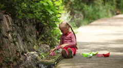 Girl is launching a toy-ship floating along the stream Stock Footage