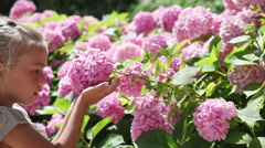 Happy little girl smelling a flower and smiling at the camera Stock Footage