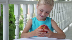 Little girl with a big red peach. Child turns it in his hands Stock Footage