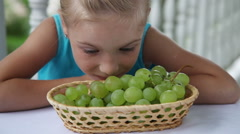 Little girl smelling grapes and smiling at the camera. She sitting at the table - stock footage