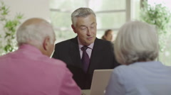 Senior couple in meeting with financial advisor or bank manager - stock footage