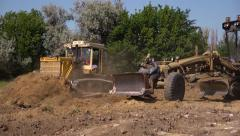 Excavator and grader during the preparation of a construction site Stock Footage