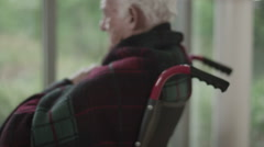 Portrait of lonely senior man in wheelchair sitting by the window Arkistovideo