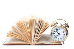 Alarm clock to stand on the open book Kuvituskuvat