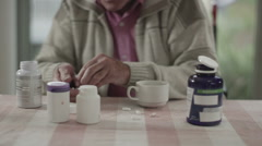 Portrait of senior man taking pills from several containers of medication - stock footage