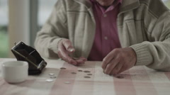 Confused senior man trying to count out coins from a purse - stock footage