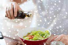close up of hands flavoring salad with olive oil - stock photo
