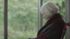 Portrait of lonely senior lady sitting by the window looking over to her meds Stock Footage