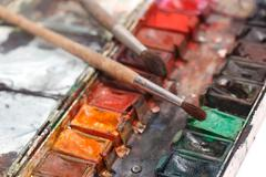 paint box with messy brushes - stock photo