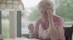Portrait of senior woman worrying about paying the bills Arkistovideo
