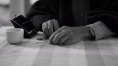b&w Confused senior man trying to count out coins from a purse - stock footage