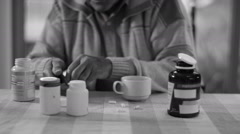 b&w Portrait of senior man taking pills from several containers of medication - stock footage