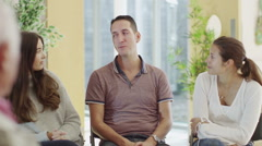 Man in group therapy session talks about his problems as the others listen - stock footage