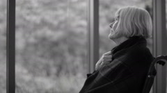 Black & white portrait of senior woman sitting by window with meds on table Stock Footage