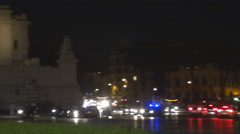 Pan left police car alert mission Rome downtown busy traffic street night people Stock Footage