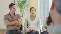 Woman in group therapy session talks about her problems as the others listen Stock Footage