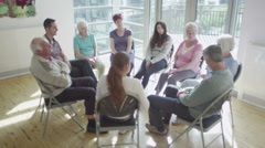 People in group therapy session talk about their problems in sunlit room - stock footage