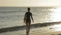 The girl in wetsuit with a surfboard comes in the sea to surf - stock footage