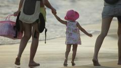 Mother with pretty baby girl and their friend are walking along the seacoast. - stock footage