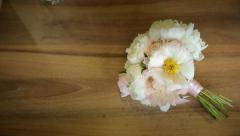 Bouquet of white flowers tied with a pink ribbon on a wooden table. Slider shot Stock Footage