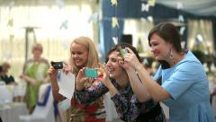 A group of girls laugh and make photo on their iphones Stock Footage